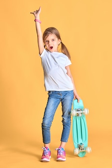 Stijlvol grappig meisje draagt een wit t-shirt, blauwe spijkerbroek en sneakers, houdt een skateboard boven de gele muur en steekt emotioneel de hand op