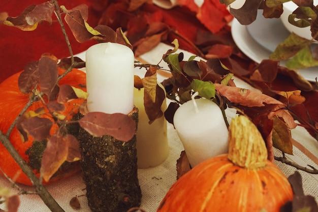 Stijlvol herfstdecoratietafeltje met pompoen en gedroogde takken