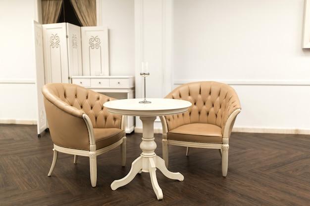 Stijlvol interieur, twee fauteuils met bruin leer, naast een salontafel in een witte kamer