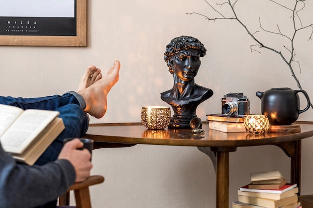 Stijlvol interieur van een privébibliotheek met houten tafel, boeken en elegante persoonlijke accessoires. de mens leest een boek over de verwaardige fauteuil. retro vintage woondecoratie. beige muur. sjabloon.