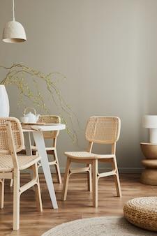Stijlvol interieur van eetkamer in gezellig huis met kopieerruimte, designstoelen, familietafel, theepot, kopjes, decoratie en elegante persoonlijke accessoires in modern interieur..