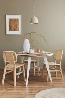 Stijlvol interieur van eetkamer in gezellig huis met wit frame, designstoelen, familietafel, theepot, kopjes, decoratie en elegante persoonlijke accessoires in modern interieur..