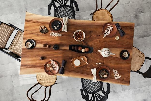 Stijlvol interieur van eetkamer met houten walnoot tafel, retro stoelen, servies, borden, tafelkleed, theepot, eten, decoratie en elegante accessoires. cementvloer. bovenaanzicht.