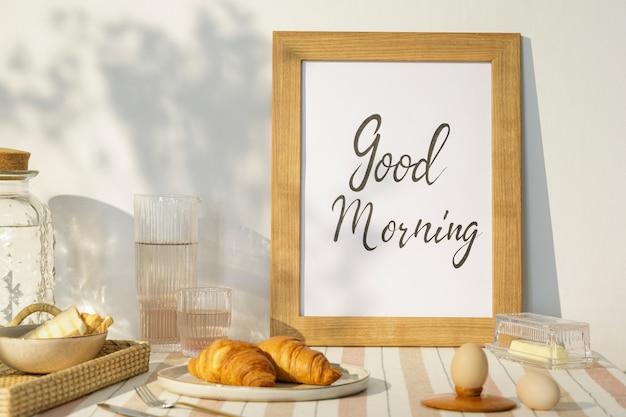 Stijlvol interieur van keukenruimte met houten tafel, bruin fotolijstje, beige tafelkleed, eten en keukenaccessoires. landelijke sfeer..