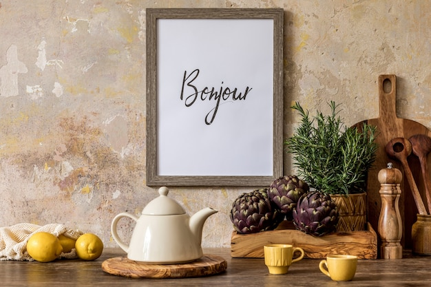 Stijlvol interieur van keukenruimte met houten tafel, bruin fotolijstje, kruiden, groenten, theepot, beker en keukenaccessoires in wabi sabi concept van home decor.