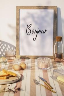 Stijlvol interieur van keukenruimte met houten tafel, bruine fotolijst, beige tafelkleed, eten en keukenaccessoires. landelijke sfeer. zomer gevoel.