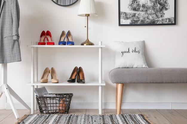 Stijlvol interieur van moderne hal met schoenen op standaard en bank