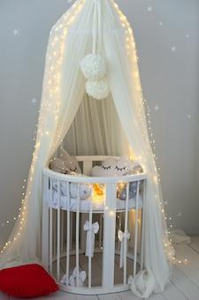 Stijlvol interieur van pasgeboren babykamer met bed hangend wit baldakijn met wieg