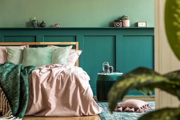 Stijlvol interieur van slaapkamer met moderne meubels, planten en elegante accessoires. plank boven het bed. mooie roze en groene lakens, dekens en kussens. modern huisdecor.