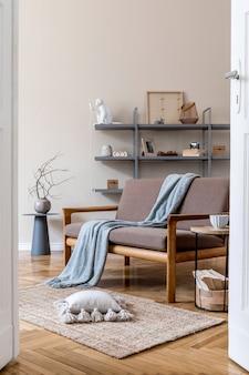 Stijlvol interieur van woonkamer in gezellig appartement met bruine houten bank, salontafel, grijze boekenstandaard, kussen, plaid en elegante accessoires. beige en japandi-concept. moderne woninginrichting. .