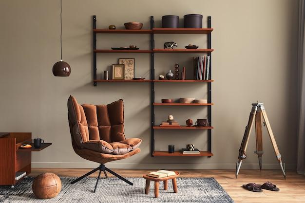 Stijlvol interieur van woonkamer met design bruine fauteuil, houten boekenkast, hanglamp, tapijtdecor, fotolijsten en elegante persoonlijke accessoires in modern retro interieur..