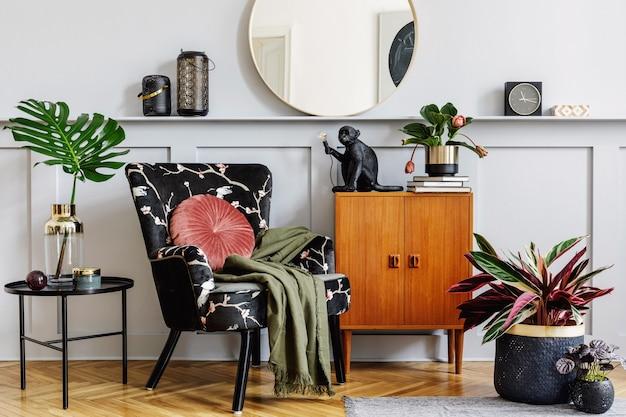 Stijlvol interieur van woonkamer met design fauteuil, houten vintage commode, ronde spiegel, plank, planten, salontafel, decoratie, lantaarn, grijze muur en persoonlijke accessoires in woondecoratie.
