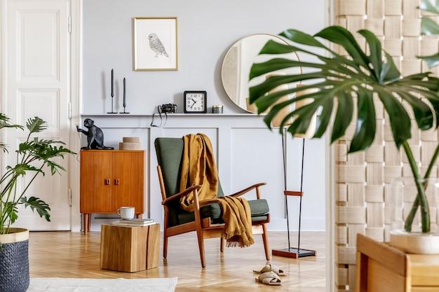 Stijlvol interieur van woonkamer met design fauteuil, houten vintage commode, ronde spiegel, plank, tropisch blad, salontafel, decoratie, tapijt en persoonlijke accessoires in woondecoratie.