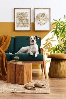 Stijlvol interieur van woonkamer met designmeubilair, gouden poef, plant, posterframes, tapijt, accessoreis en mooie hond liggend op de bank in gezellig interieur