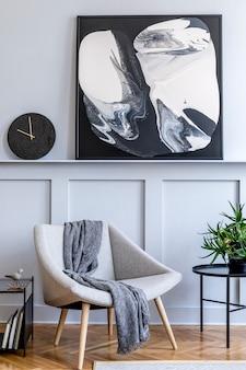 Stijlvol interieur van woonkamer met grijze design fauteuil, kussens, marmeren kruk, schilderijen, cactussen, decoratie, zwarte klok en elegante persoonlijke accessoires in een modern interieur.