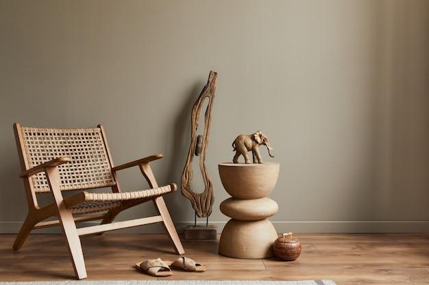 Stijlvol interieur van woonkamer met rotan fauteuil, houten kruk, olifant figuur en decoratie in modern interieur. ruimte kopiëren.