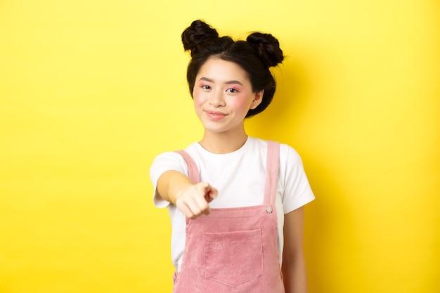 Stijlvol japans meisje met schoonheid make-up wijzend op de camera, lacht naar je, wenkt en nodigt mensen uit, staande op geel.
