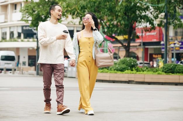 Stijlvol jong chinees stel hand in hand en pratend tijdens het wandelen in de stad in het weekend