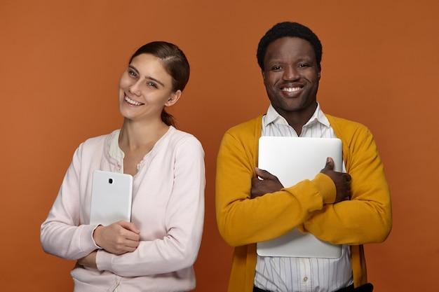 Stijlvol jong gemengd ras team van twee collega's met behulp van elektronische gadgets voor werk, positieve vrolijke witte vrouw met digitale tablet en knappe lachende zwarte man omhelst laptopcomputer