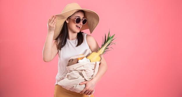 Stijlvol jong meisje in grote hoed en zonnebril glimlacht en houdt een eco-tas met exotisch fruit