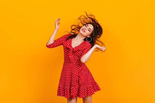 Stijlvol jong meisje in rode korte jurk speelt haar. portret van brunette in hoepeloorringen op gele muur.