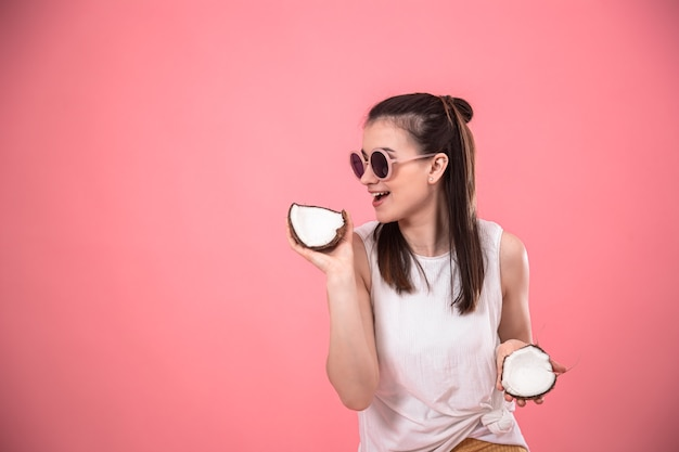 Stijlvol jong meisje in zonnebril glimlacht en houdt fruit op een roze achtergrond. zomer vakantie concept.