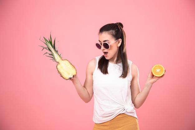 Stijlvol jong meisje in zonnebril houdt fruit. zomer vakantie concept.