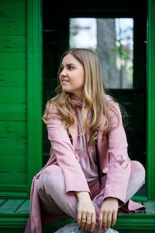 Stijlvol jong meisje met blond haar van europees uiterlijk zit op de trap, gekleed in een roze pak, moderne damesmode, vrijetijdskleding