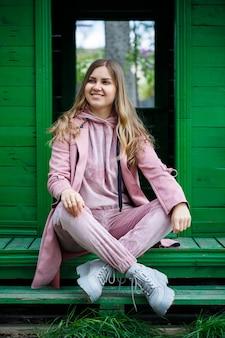 Stijlvol jong meisje met blond haar van europees uiterlijk zit op de trap, gekleed in een roze pak, vrijetijdskleding