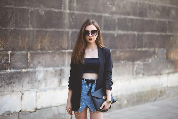 Stijlvol jong meisje met bril en een lederen tas in haar handen staat in de buurt van de stadsmuur