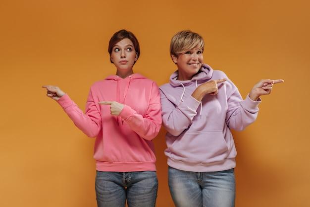 Stijlvol jong meisje met donkerbruin haar in roze trui wijzende vingers naar kant samen met oude dame met moderne outfit op oranje achtergrond.
