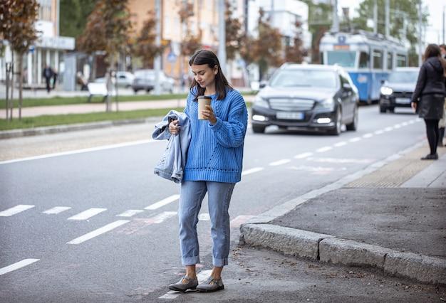 Stijlvol jong meisje met koffie om te gaan wandelen in de stad