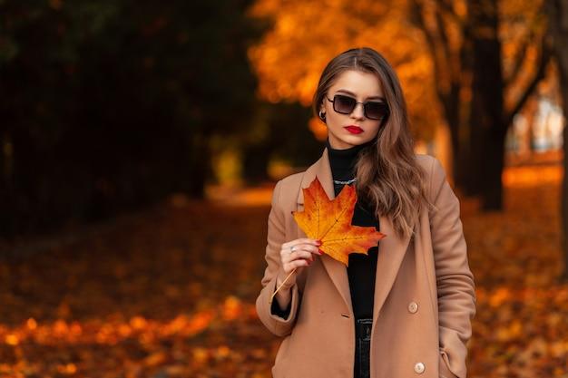 Stijlvol jong meisje met zonnebril in een modejas en een trui met een oranje herfstblad loopt in het park