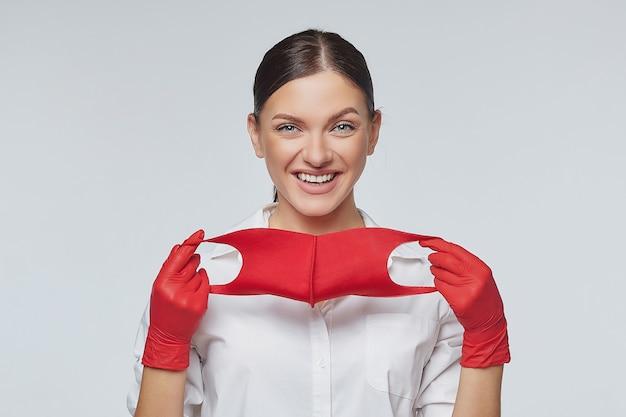 Stijlvol jong meisje zet rood gezichtsmasker en handschoenen aan.