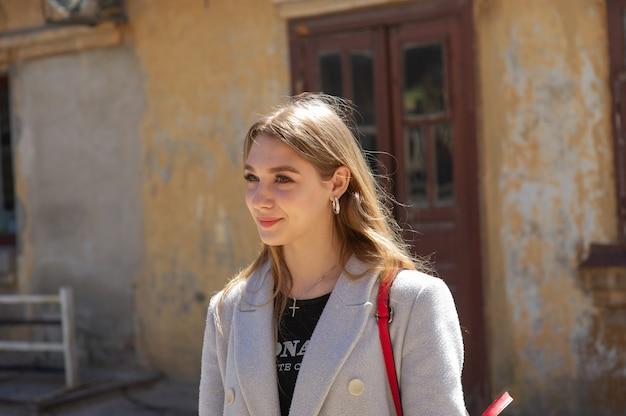 Stijlvol jong mooi meisje in een grijze jas kijkt naar de camera en glimlacht lichtjes tegen de achtergrond van de stad. een