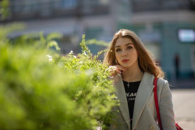 Stijlvol jong mooi meisje in een grijze jas kijkt naar de camera en glimlacht lichtjes tegen de achtergrond van de stad. het meisje staat bij een groene struik.