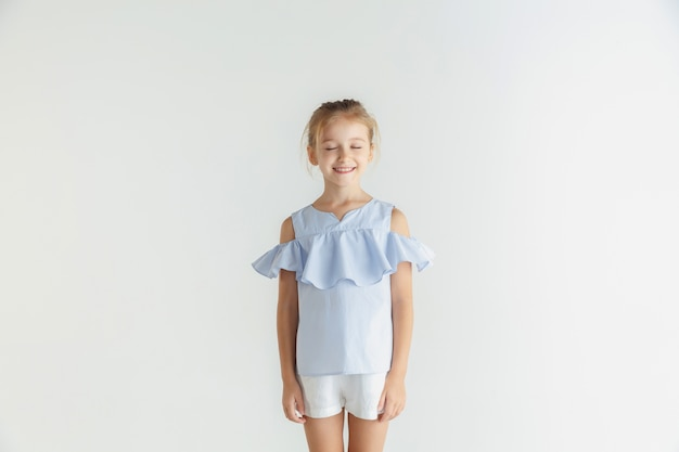 Stijlvol klein glimlachend meisje poseren in casual kleding geïsoleerd op een witte muur. kaukasisch blond vrouwelijk model. menselijke emoties, gezichtsuitdrukking, kindertijd. dromen met gesloten ogen.