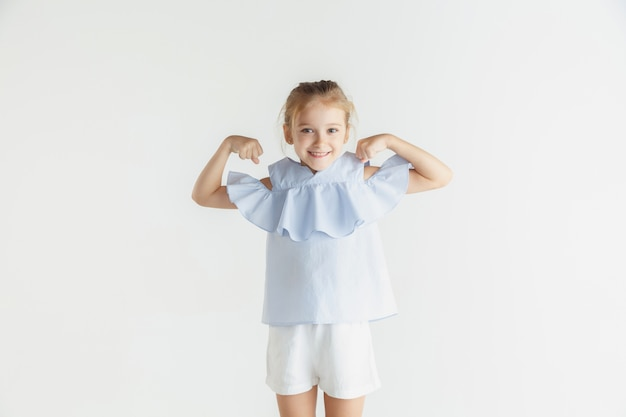 Stijlvol klein glimlachend meisje poseren in casual kleding geïsoleerd op een witte muur. kaukasisch blond vrouwelijk model. menselijke emoties, gezichtsuitdrukking, kindertijd. winnen, vieren, glimlachen.