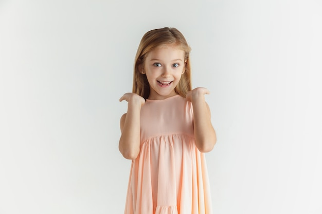 Stijlvol klein glimlachend meisje poseren in jurk geïsoleerd op een witte studio achtergrond. kaukasisch blond vrouwelijk model. menselijke emoties, gezichtsuitdrukking, kindertijd. glimlachend, verbaasd, verwonderd.