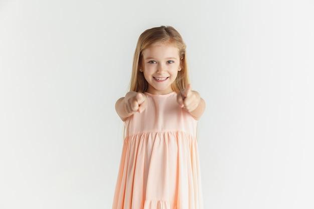 Stijlvol klein glimlachend meisje poseren in jurk geïsoleerd op een witte studio achtergrond. kaukasisch blond vrouwelijk model. menselijke emoties, gezichtsuitdrukking, kindertijd. op camera wijzen, kiezen.