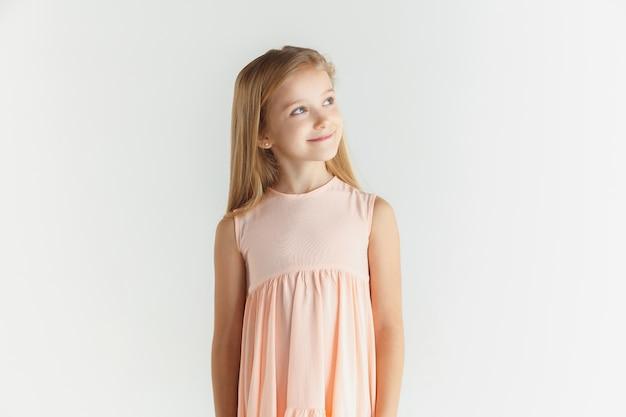 Stijlvol klein glimlachend meisje poseren in jurk geïsoleerd op witte studio