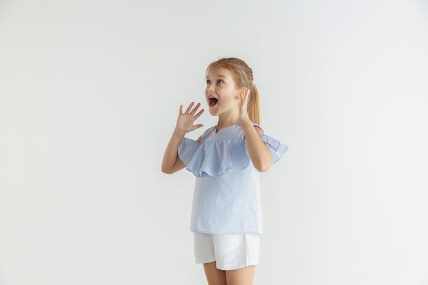 Stijlvol klein glimlachend meisje poseren in vrijetijdskleding geïsoleerd op witte ruimte. kaukasisch blond vrouwelijk model. menselijke emoties, gezichtsuitdrukking, kindertijd, verkoop