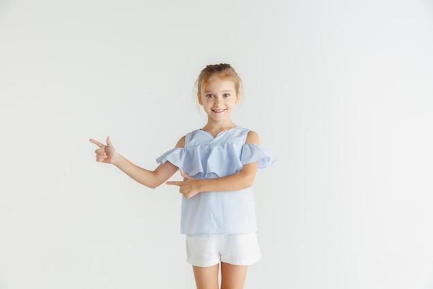 Stijlvol klein glimlachend meisje poseren in vrijetijdskleding geïsoleerd op witte studio achtergrond. kaukasisch blond vrouwelijk model. menselijke emoties, gezichtsuitdrukking, jeugd. wijzend op lege spatiebalk.