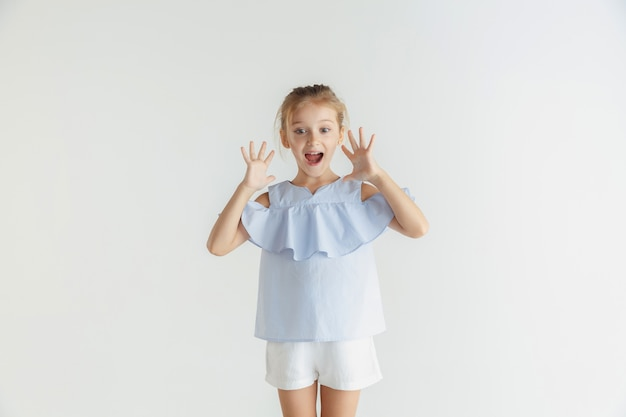 Stijlvol klein glimlachend meisje poseren in vrijetijdskleding geïsoleerd op witte studio achtergrond. kaukasisch blond vrouwelijk model. menselijke emoties, gezichtsuitdrukking, kindertijd, verkoop. geschokt, verbaasd.
