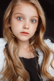 Stijlvol klein meisje poseren in witte outfit geïsoleerd op zwarte muur. het stellen van het mooie kaukasische blonde vrouwelijke model. menselijke emoties, gezichtsuitdrukking, kindertijd, mode, stijl.