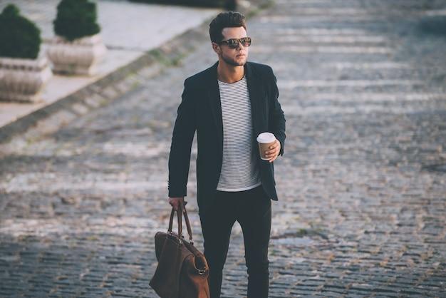 Stijlvol knap voor onderweg. knappe jonge man in slimme vrijetijdskleding draagtas en koffiekopje tijdens het wandelen langs de straat
