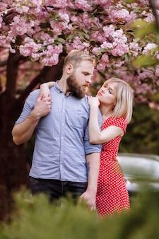 Stijlvol koppel bij de sakura boom met bloeiende roze bloemen. mooie jonge paar, man met baard en blonde vrouw knuffelen in het voorjaar park.