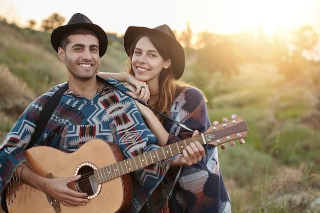 Stijlvol koppel met gitaar op veld