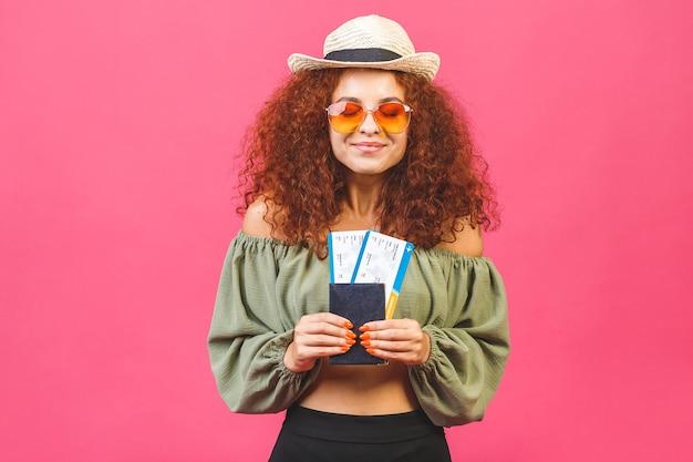 Stijlvol krullend jong meisje of vrouw in een strooien hoed met zonnebril geïsoleerd op roze achtergrond