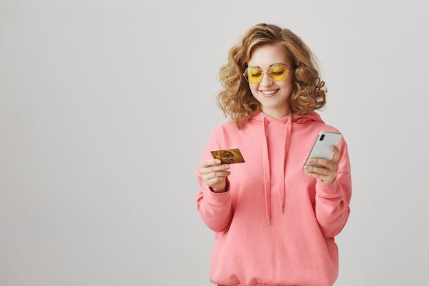 Stijlvol krullend meisje dat online winkelt, met creditcard en smartphone